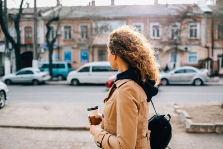 Young woman with curly hair in a beige coat walks around the city with coffee