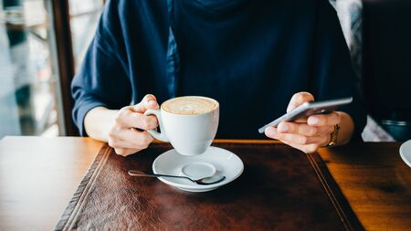 Close-up of a woman in a cafe holding a mobile phone and a cup of coffee Banco de Imagens