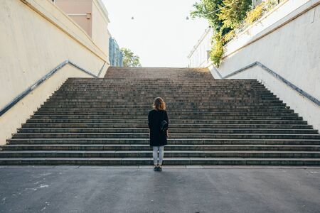 Woman with curly hair stands near the city stairs