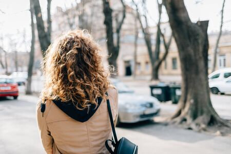 Young woman with curly hair in a beige coat walks around the city Banco de Imagens