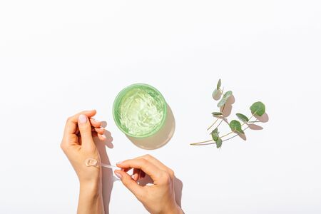Woman's hands applying sample of aloe vera gel next to eucalyptus branches on white table, cosmetic flat lay composition. 免版税图像