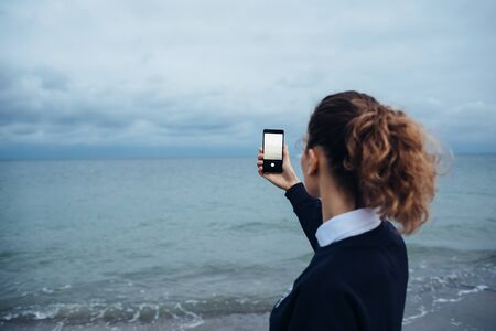 Woman with curly hair photographs the sea on a mobile phone Banco de Imagens