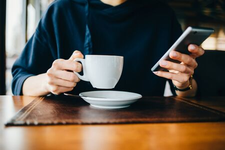 Close-up woman in a blue sweater uses a mobile phone and drinks coffee in a cafe