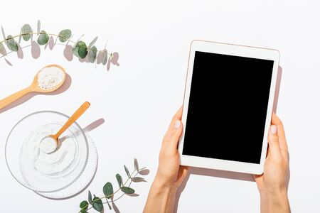 Flat layout females hands holding blank-screen tablet device next to homemade organic cosmetics clay mask on white table, top view.
