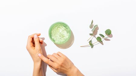 Females hands applying aloe vera gel near eucalyptus branches on white table, natural cosmetic flat lay composition. Banco de Imagens