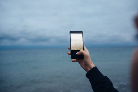 Close-up of a woman photographing sea on a mobile phone