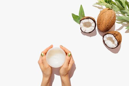 Flat lay womans hands holding jar of natural coconut oil next to fresh cracked and whole coconut with green leaves on white background, top view.