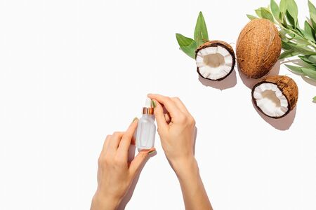 Womans hands holding bottle with natural cosmetic coconut oil next to fresh coconuts and green leaves on white background with copy space, top view.