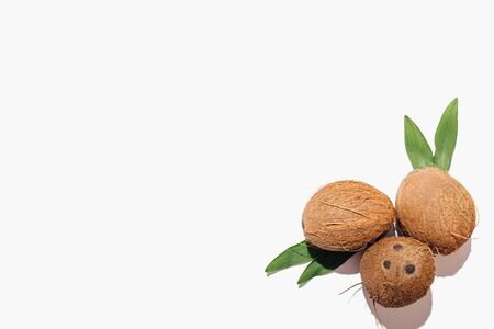 Coconuts with green leaves in corner of white background, flat lay composition with copy space.