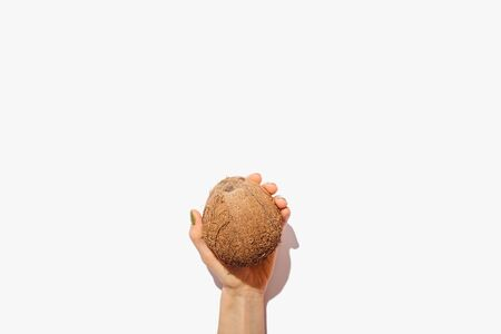 Minimal flat lay composition of female hand holding one coconut on white background, view from above. Stockfoto