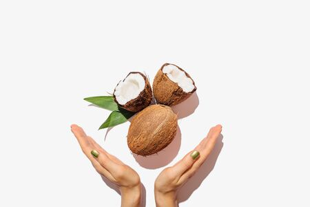 Female hands with green manicure hold open and whole coconuts and fresh leaves on white background, flat lay composition.