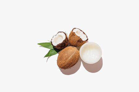 Natural coconuts next to jar of oil and green leaves on white background, minimal flat lay composition. Stockfoto