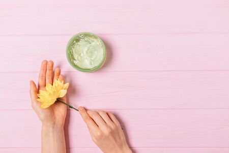 Female hands holding fresh yellow flower next to jar of aloe cosmetic gel on pink background with copy space, flat lay. Banco de Imagens - 133593222