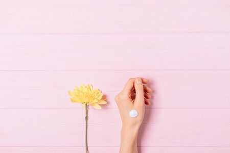 Womans hand with drop of cosmetic cream applied next to fresh yellow flower on pink table, flat lay.