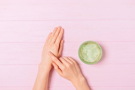 Female hands apply aloe gel on skin next to jar of cosmetic product on pink table, flat lay. Banco de Imagens - 133593673