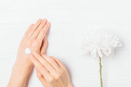 Die Hände der Frau, die nahrhafte Lotion auf der Haut neben blühender Chrysanthemeblume auf weißem Holztisch auftragen, flach legen. Standard-Bild