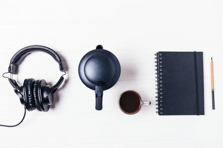 Flat lay black notebook, pencil, coffee, moka pot and headphones on white wooden table, top view