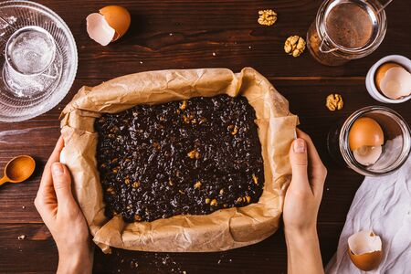 Female hands holding baking dish with dough to bake delicious brownie cake, flat lay composition on rustic dark background. Zdjęcie Seryjne