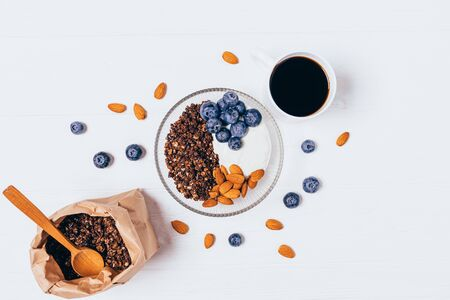 Healthy breakfast granola bowl with blueberries and yogurt next to cup of coffee on white table, top view.