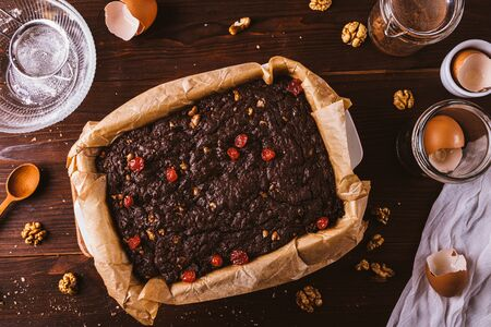 Cooked brownie cake in baking dish with parchment among ingredients on dark wooden table, flat lay. Zdjęcie Seryjne