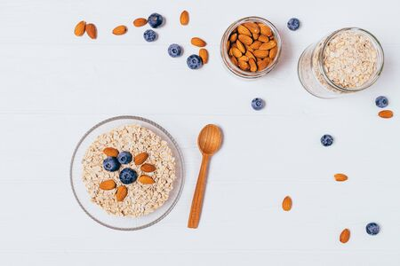 Bowl of oatmeal flakes, almonds and fresh blueberries on white table with copy space, top view. Zdjęcie Seryjne