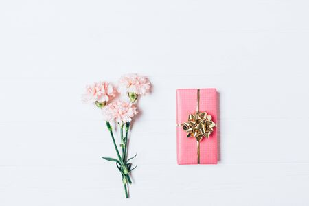 Top view of bouquet and gift box. Flat lay composition with pink flowers and present on white background.