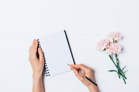 Female hand writing in empty notebook near bouquet of fresh flowers on white wooden table, flat lay.