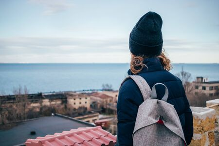 Rear view of young woman with backpack standing on the roof looking at city and sea.