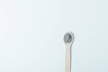 Black clay cosmetic dry powder in wooden spoon on white background with copy space, minimal flat lay.