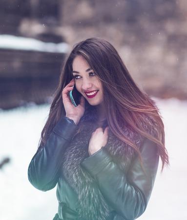 visone: Portrait of beautiful brunette girl talking by phone in snowy winter time Archivio Fotografico