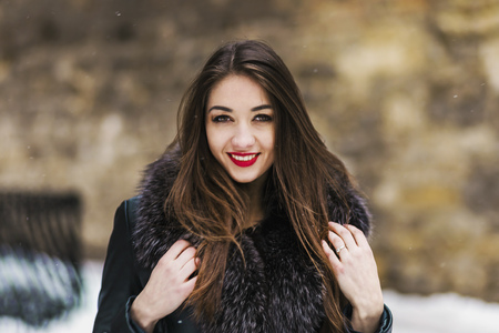 Portrait of beautiful brunette girl having fun in snowy winter time