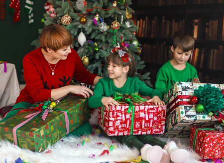 hapiness: Mother with her happy kids have got gift boxes under Christmas tree