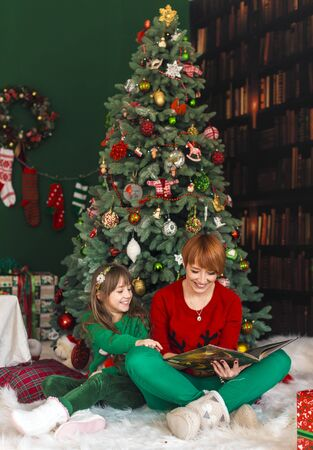seated: Mother with her daughter reading the book near dressed up christmas tree