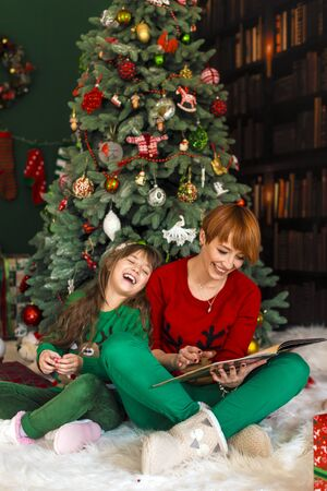 Mother with her daughter reading the book near dressed up christmas tree