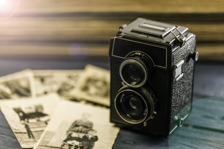 Studio shot of old vintage photo camera with pictures on wooden background