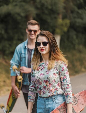 Boy and girl, hipster stylish teenagers wearing sunglasses are walking through the park holding skateboards in hands, teen freedom concept Stock Photo