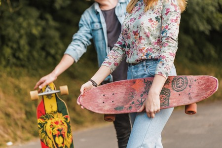 Boy and girl, hipster stylish teenagers wearing sunglasses are walking through the park holding skateboards in hands, teen freedom concept Stockfoto