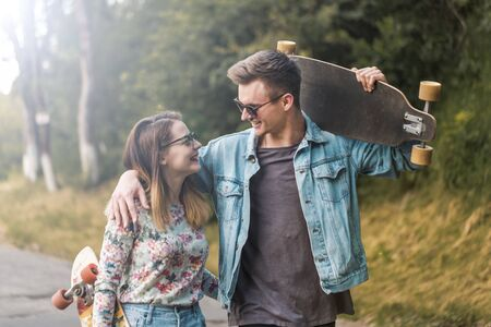 Cute hipster couple with sunglasses holding skateboards Stock Photo