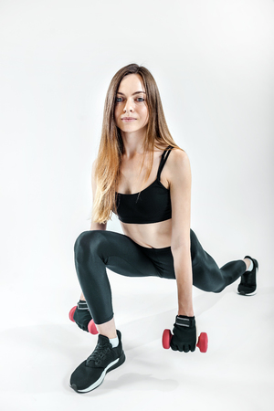 Low section of a sportswoman holding pink dumbbells wears black leggins o nwhite isolated background