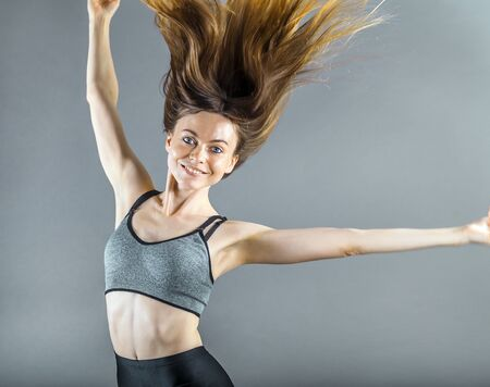 sportwoman: Pretty dark hair sportswoman wearing a grey top in the grey isolated background