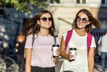 Two pretty caucasian girlfriends in sunglasses, with backpacks, are holding coffee and walking along the street joyfully, sunny day