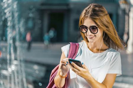 Pretty smiling caucasian tourist girl in stylish sunglasses is holding smartphone before the city fountain, sunny day view Archivio Fotografico