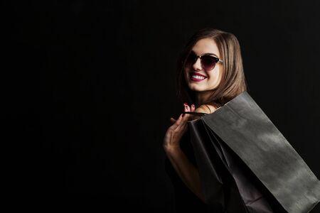 Elegante Brunettefrau trägt die Sonnenbrille und schwarzes Kleid, die schwarze Einkaufstaschen, schwarzes Freitag-Konzept halten