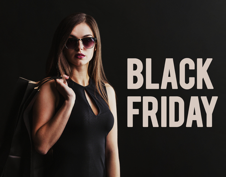 エレガントなブルネットの女性身に着けているサングラスと黒いドレス持株黒いショッピング バッグ、黒金曜日コンセプト 写真素材 - 89136005