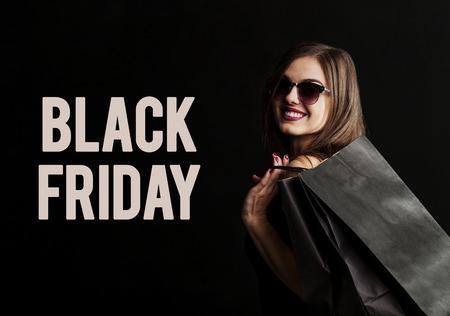 Élégante femme brune porte des lunettes de soleil et robe noire tenant des sacs à provisions noirs, concept de vendredi noir