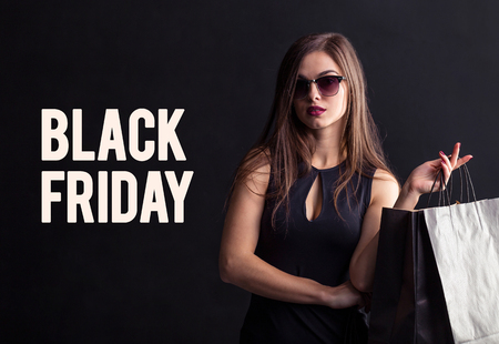 Elegant brunette woman wears sunglasses and black dress holding black shopping bags, black friday concept 版權商用圖片 - 89136160