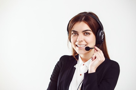 Cheerful brunette woman, kindly callcenter operator, wear black jacket and headphone set, smiling before white isolated background