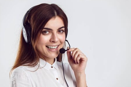 Cheerful brunette woman, kindly callcenter operator, wear black white shirt and black headphone set, smiling before white isolated background Stock Photo