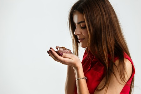 Woman wears red shirt holds decorative aromatic soap on white background Stock Photo