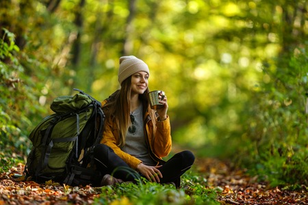 Beautiful brunette tourist girl wears cap and backpacked have break with cup of tea sitting in the forest, autumn tourism concept